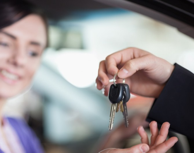 Woman in a car receiving keys from a car dealer